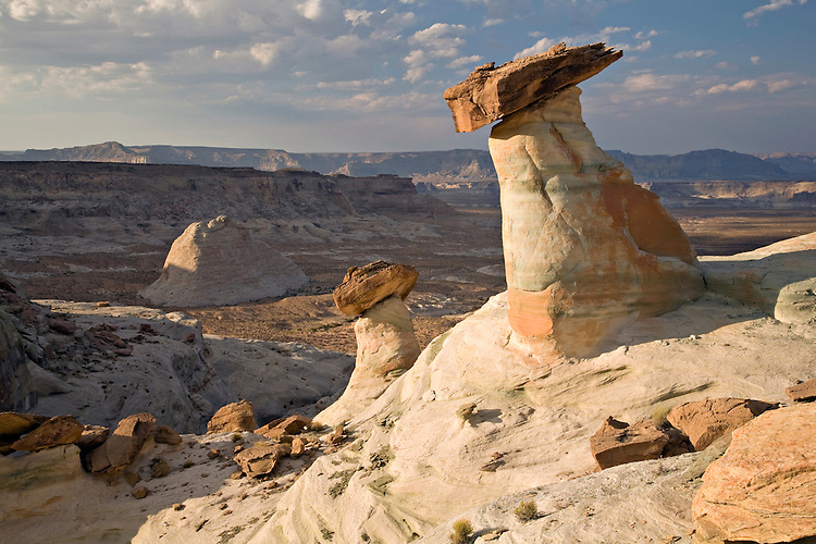On the Colorado Plateau, many hoodoos made of Navajo sandstone are capped by iron cemented sandstone.