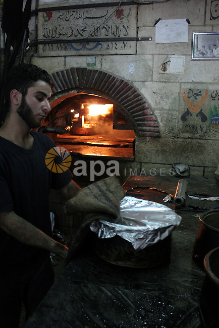 "Palestinian bakers prepare jars full of rice and meat 'Qedrah"" in a traditional stove in the West Bank city of Hebron on August 30, 2010 during the holy fasting month of Ramadan, when observant Muslims abstain from eating, drinking and smoking from sunrise to sunset . Photo by Mamoun Wazwaz"