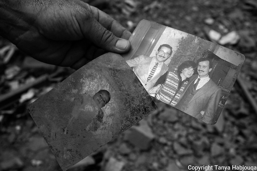 A man holds up two family photographs rescued from the rubble?not his own, but from one of the hundreds of homes devastated by the war in the southern suburbs of Beirut.