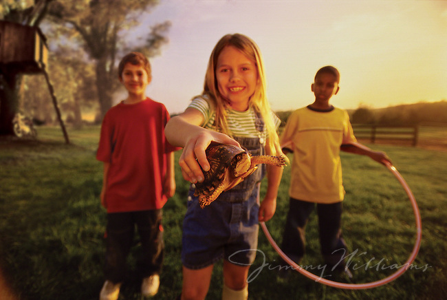 A young girl shows off her pet turtle while playing with her 2 friends