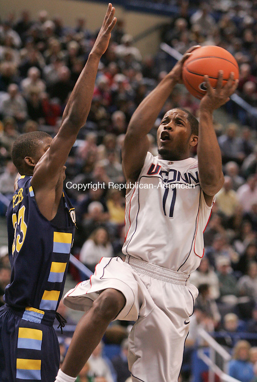HARTFORD, CT- 30 JANUARY 2010-013010JS09--UConn's Jerome Dyson (11) puts up a shot in front of Marquette's Jimmy Butler (33) during their game Saturday at the XL Center in Hartford. <br /> Jim Shannon Republican-American