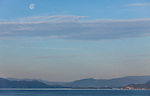 The nearly-full moon is seen above a hazy Flathead Lake, Montana near sunset.
