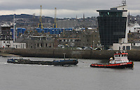 A tugboat MTS Indus leaves Aberdeen harbour pulling a barge with the Aberdeen Navigational Control Centre.