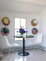 The intimate dining area has a small round table with a pair of Eames chairs