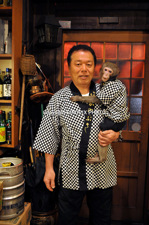 Fuku-chan, 6, a Japanese monkey waiter, with is owner Mr Otsuka, at an Izakaya bar in  north of Tokyo, Japan. The six year old monkey looks after the guests hot towels by taking them from the steamer oven and delivering them to all guests. The bar is extremely popular amongst people from all over Japan who come to see the monkey waiters.