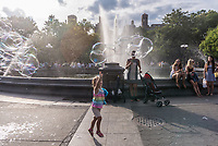 New York, NY, USA - 13 August 2017 - A young girl chases a spray of bubble spray on a hot summer's day in Washington Square Park