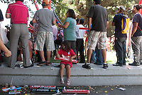 Los Angeles, CA -  Sunday, June 22, 2014: One young fan pays attention to thundersticks as thousands of Koreans watched the South Korea vs. Algeria first round match on the  front lawn of Wilshire Park Place.