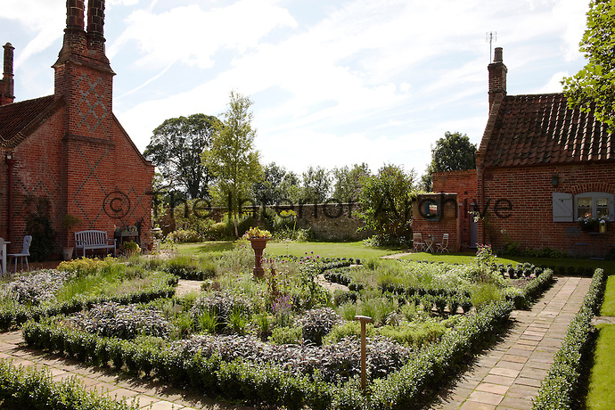 Mellow brick paths and neat box hedging line the herb garden situated between the rear of the house and an outbuilding containing Sheila Scholes' studio