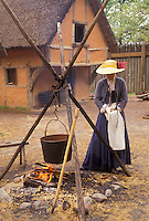 AJ3408, Jamestown Settlement, Jamestown, Virginia, Woman costumed interpreter demonstrates cooking outside on an open fire at James Fort at the Jamestown Settlement, a living-history complex, in the state of Virginia.