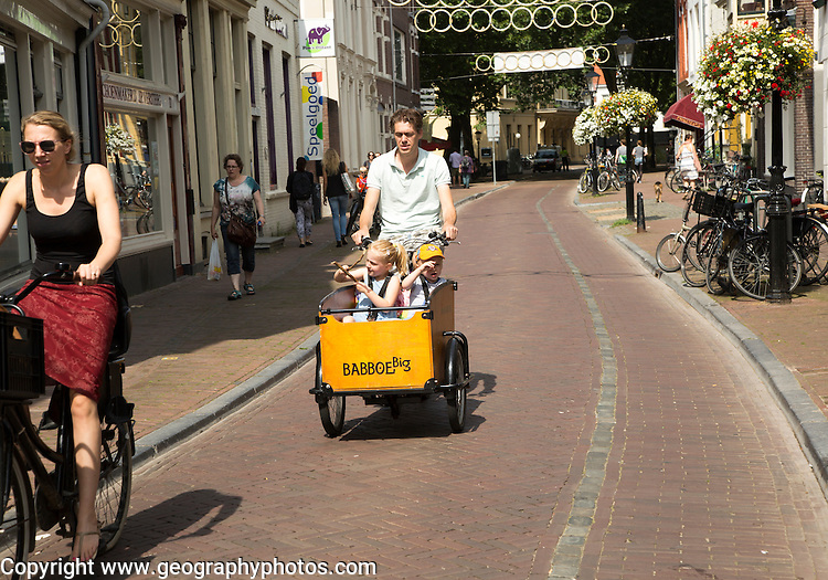 Man carrying two children in Babboe Big box on his cargo bike bicycle, Utrecht, Netherlands