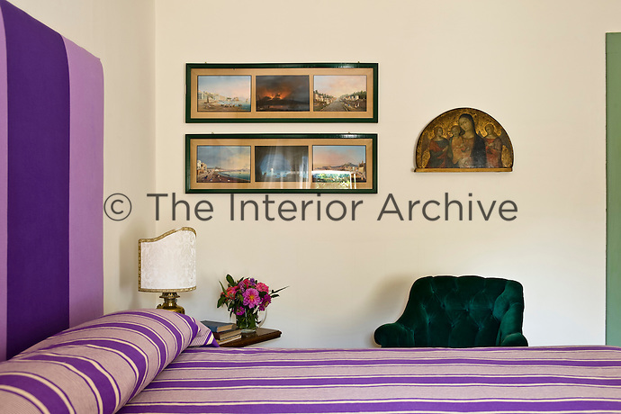 Contemporary photography hangs alongside an antique painting of a Madonna and child in one of the bedrooms at Villa Barberina