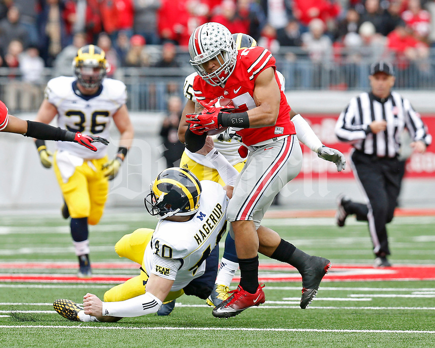 Ohio State Buckeyes running back Jalin Marshall (17) slips by Michigan Wolverines punter Will Hagerup (40)during a punt return in the 1st quarter of their game at Ohio Stadium in Columbus, Ohio on November 29, 2014.  (Dispatch photo by Kyle Robertson)