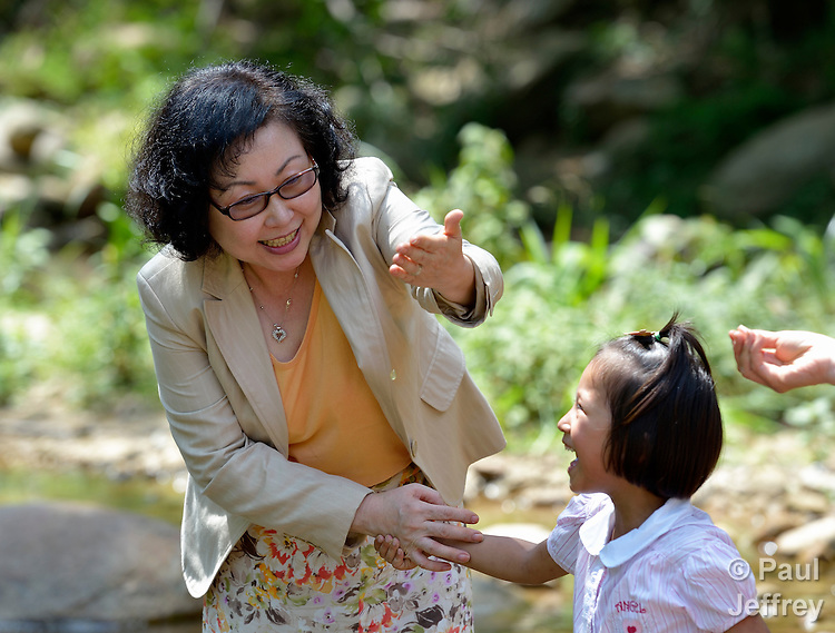 Cindy Moon, a United Methodist missionary, holds out a spider web as she walks along a river in the hill country of northern Thailand with one of the girls living in an orphanage she founded with her husband Gary in Chiang Mai. The girls are orphans, and are all HIV positive.