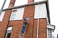Fixing the Malcom X, Marshall Street Blue Plaque  into situ