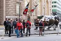 Tourists pose for pictures by the Charging Bull bull statue on Broadway in the Financial District of New York City.