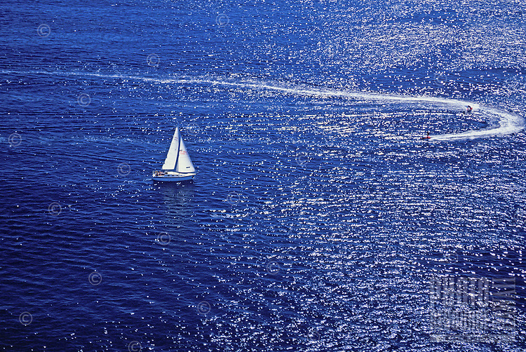 Two jet skiers create a white circular wake while a  sailboat peacefully skims the steely blue ocean nearby.