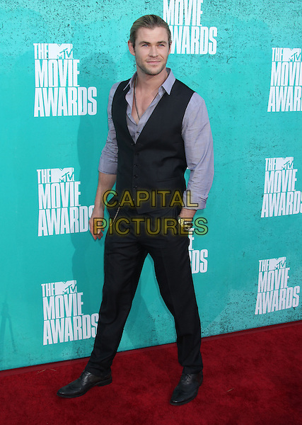 Chris Hemsworth.2012 MTV Movie Awards held at the Gibson Amphitheatre, Universal City, California, USA..June 3rd, 2012.full length trousers purple shirt black waistcoat hand in pocket .CAP/ADM/RE.©Russ Elliot/AdMedia/Capital Pictures.