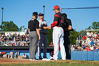 Batavia Muckdogs manager Mike Jacobs (28) shakes hands with Jerad Head (11) during the lineup exchange with umpires Drew Saluga (right) and Jennifer Pawol (left) before a game against the Auburn Doubledays on July 4, 2017 at Dwyer Stadium in Batavia, New York.  Batavia defeated Auburn 3-2.  (Mike Janes/Four Seam Images)