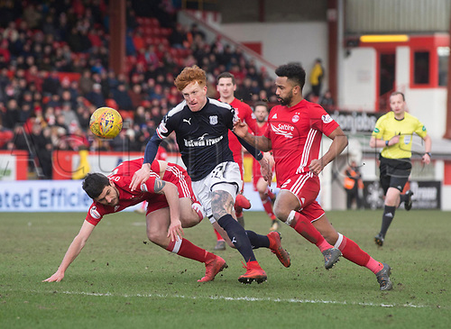 17th March 2018, Pittodrie Stadium, Aberdeen, Scotland; Scottish Premier League football, Aberdeen versus Dundee; Simon Murray of Dundee bursts between Anthony O'Connor and Shaleum Logan of Aberdeen
