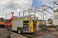 Fire Appliance at the scene of an Industrial unit where Firefighters are damping down the remains of a fire. This image may only be used to portray the subject in a positive manner..©shoutpictures.com..john@shoutpictures.com