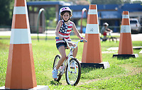 NWA Democrat-Gazette/DAVID GOTTSCHALK Eva Kirk, 8, rides through large cone obstacles Monday, July 8, 2019, during the Breakaway Cycling Team Bike Skills Training Camp at the Runway Bike Park at the Jones Center in Springdale. The two day camp emphasizes skills, etiquette and safety. Today the campers will be on the Greenway Trail System.