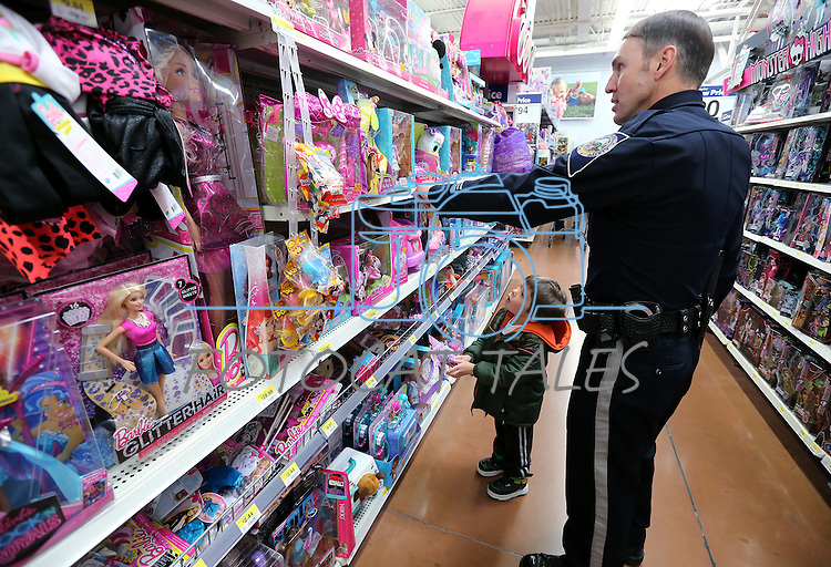 NHP Sgt. Todd Hartline shops with a student during the 11th annual Holiday with a Hero at Walmart in Carson City, Nev., on Wednesday, Dec. 16, 2015. <br /> Photo by Cathleen Allison