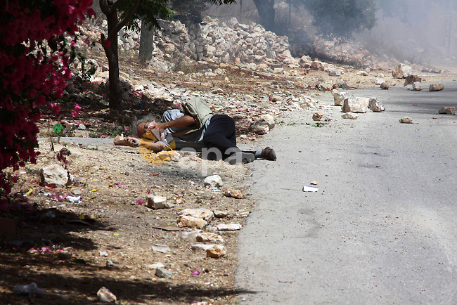 "A Palestinian man lays on the ground as he suffers from exposure to tear gas which was fired by Israeli security forces during clashes following a demonstration against the expropriation of Palestinian land by Israel in the village of Kfar Qaddum, near Nablus, in the occupied West Bank on June 6, 2013, as Palestinians across the West Bank and the Gaza Strip hold rallies to mark the Naksa (setback). Palestinians mark ""Naksa Day"" to mourn the 46th anniversary of Israel's occupation of the West Bank and Gaza Strip in the Six-Day War. Photo by Nedal Eshtayah"