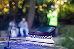 © Joel Goodman - 07973 332324 . 16 August 2013 . Manchester , UK . For stock - traffic police officer's hat on top of an unmarked police car as in the background a policeman watches over two youths . Drive along with Inspector Matt Bailey-Smith ( 16366 ) of Greater Manchester Police 's Serious Collision Unit . Photo credit : Joel Goodman