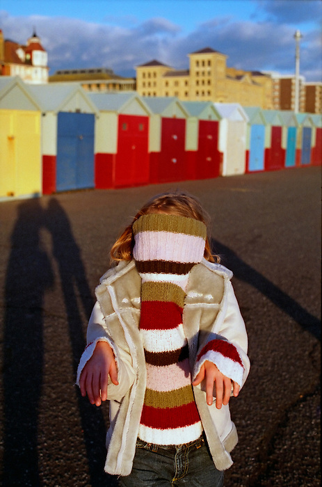 A girl pulls her jumper over her head on a cold day in Brighton. England 2005.