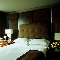 In the master bedroom a folding screen placed behind the bed provides a backdrop for the suede headboard