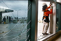 Shaun Jones, of Bam Contracting, works on a broken window in the main terminal at Lambert- St. Louis International Airport on April 23, 2011 after storms last night damaged both the interior and exterior of the airport. The airport was closed all day today and officials hope to reopen tomorrow. REUTERS/Sarah Conard (UNITED STATES)