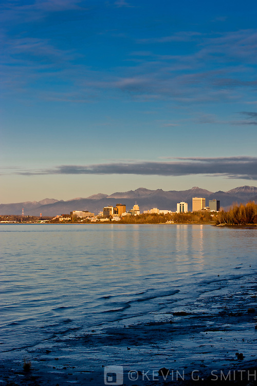 The Anchorage City Skyline reflected in the waters of Knik arm just before sunset, high tide, taken from the Tony Knowles Coastal Trail, fall, Southcentral Alaska, USA.
