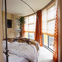 In this bedroom the design of the wrought-iron bed echoes the curving line of the circular wall