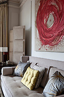 Silk scatter cushions on the sofa below a large red abstract painting