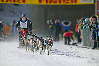 Musher Egil Ellis, at the start of the oldest continuously run sled dog race in the world, the 2003 Open North American Sled dog championships which start on the Chena River in downtown Fairbanks, Alaska. The annual race consists of three daily races, the combined fastest time wins.