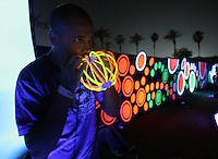 Indio, Ca- Zack Martin of Dallas, Tx. builds a glow-in-the-dark ball, relaxing near the dance tents at Coachella Valley Music and Arts Festival, Saturday night, April 29 2006.