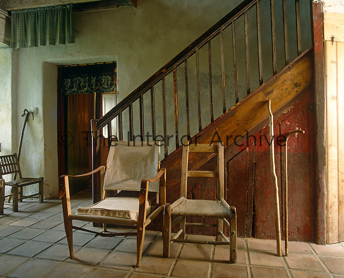 A 'famine' chair on the left with a Victorian campaign chair and a 'sugawn' chair infront of the orignal wooden staircase in the tiled entrance hall