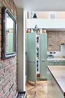 A pale green kitchen unit opens up to reveal a fridge, the top of which houses a collection of ceramic jugs