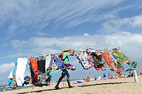 URUGUAY Jose Ignacio, beach at atlantic ocean, flying seller carry garments on yoke