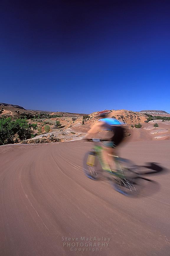 Mountain biker speeding along the striated sandstone of Bartlett Wash, Moab, Utah