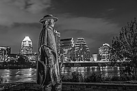 This is a photo we captured of Stevie Vaughan statue as he looks over ladybird lake, auditorium shores with the Austin Skyline in the background in black and white.