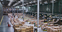 Large warehouse facility with forklifts, freight, people.