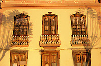 Boarded up windows with shadows of trees on the building. La Palma, Canary Islands. April 2006