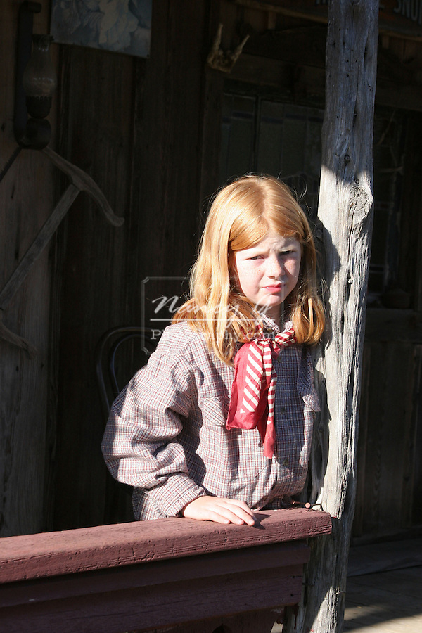 A young cowgirl in an old west town