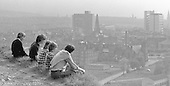 "Lads looking at a magnificent view of Edinburgh from ""Arthur's Seat"", a steep granite hill, Edinburgh, Scotland, 1979.  John Walmsley was Photographer in Residence at the Education Centre for three weeks in 1979.  The Education Centre was, at the time, Scotland's largest purpose built community High School open all day every day for all ages from primary to adults.  The town of Wester Hailes, a few miles to the south west of Edinburgh, was built in the early 1970s mostly of blocks of flats and high rises."