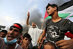 Palestinian protesters gather during clashes with Israeli troops in tents protest where Palestinians demand the right to return to their homeland at the Israel-Gaza border, in Khan Younis in the southern Gaza Strip on October 19, 2018. Photo by Ashraf Amra
