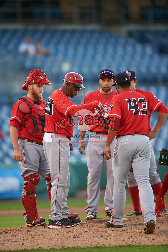 Louisville Bats manager Delino DeShields (90) hands the ball to relief pitcher Wandy Peralta (43) as Chris Berset (10) and Hernan Iribarren (2) look on during a game against the Syracuse Chiefs on June 6, 2016 at NBT Bank Stadium in Syracuse, New York.  Syracuse defeated Louisville 3-1.  (Mike Janes/Four Seam Images)