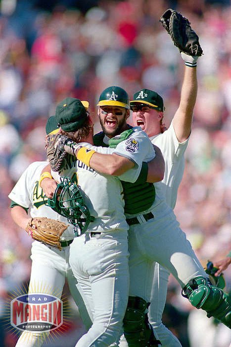 OAKLAND, CA - Mark McGwire, Terry Steinbach and Carney Lansford of the Oakland Athletics celebrate after winning Game 4 of the American League Championship Series against the Boston Red Sox at the Oakland Coliseum in Oakland, California in 1990. Photo by Brad Mangin