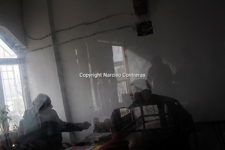 February 13, 2016: Syrian refugee workers are seen reflected in a window as Sherif Khalil (left bottom), a 51 years-old Syrian kurdish refugee from Aleppo, sits at the office of his print factory in Gaziantep. Sherif is a businessman that fled into Turkey during the war in the neighbouring country and currently owns a factory that also gives job to other refugees from Syria.