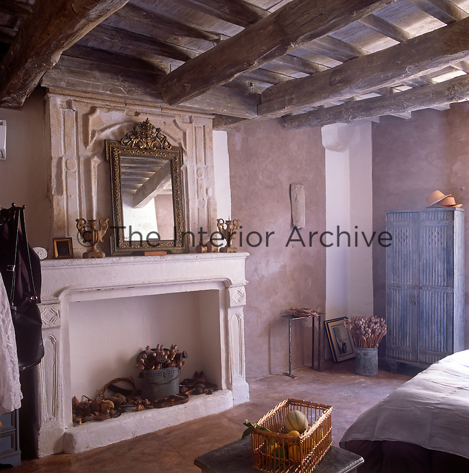 A rustic style bedroom with a beamed ceiling and stone floor. A limed distressed finish covers the walls. A gilt mirror resting on a plaster plaque sits atop a stone fireplace.